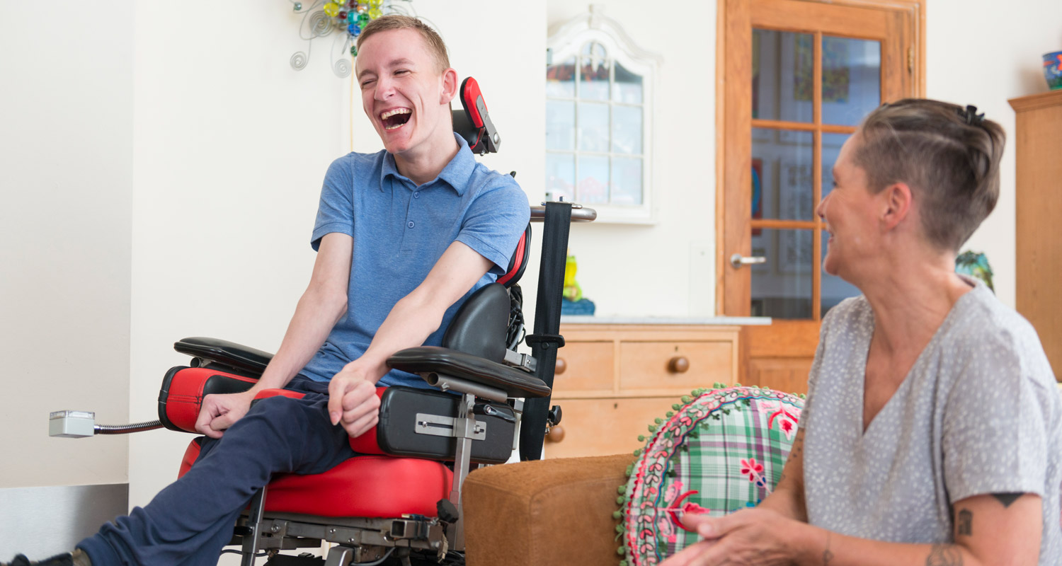 man smiling in wheelchair and mentor sitting next to him on couch