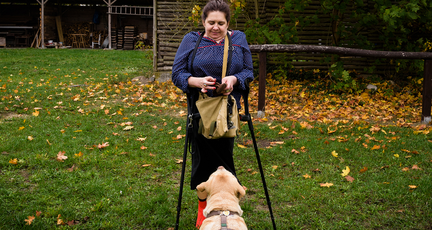 Female rehabilitation patient with canes in park with dog