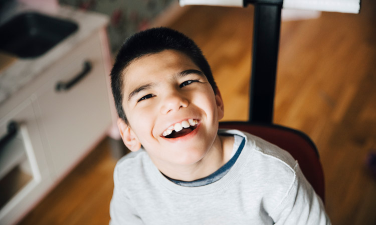 boy with autism sitting and smiling