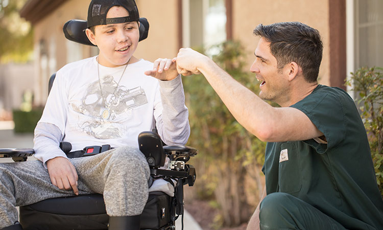 Young male patient in wheelchair fist bumping male nurse