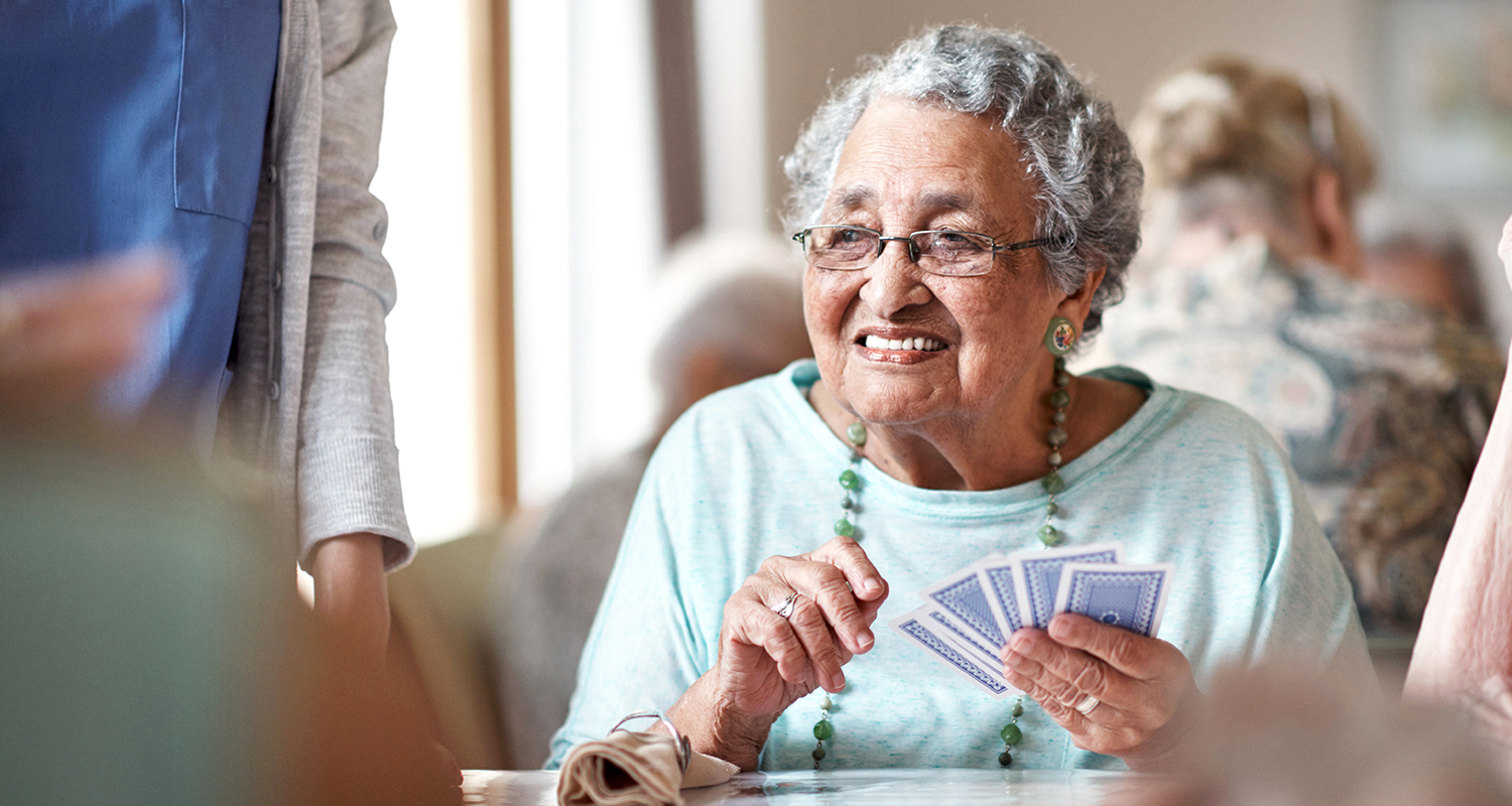 senior lady playing cards with friends