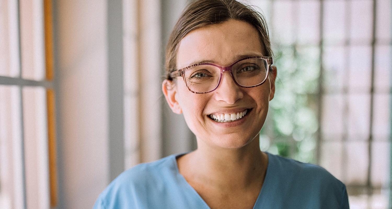 nurse smiling next to window in scrubs