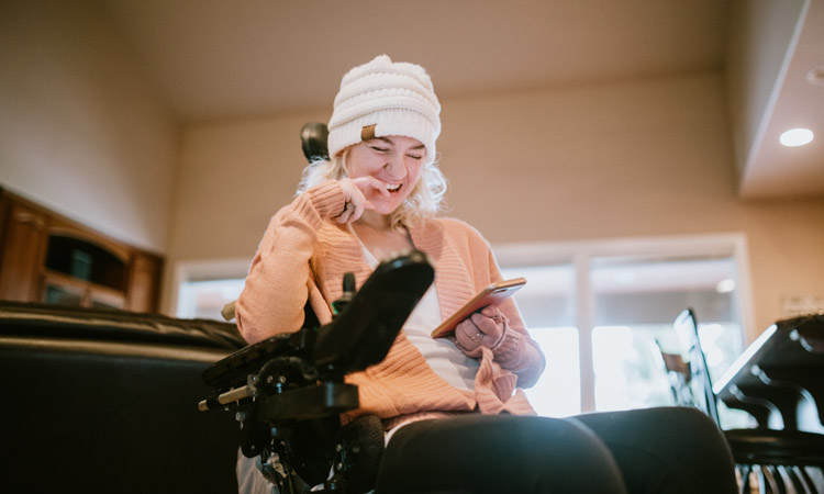 young woman in winter hat sitting in wheelchair and smiling at something on her phone