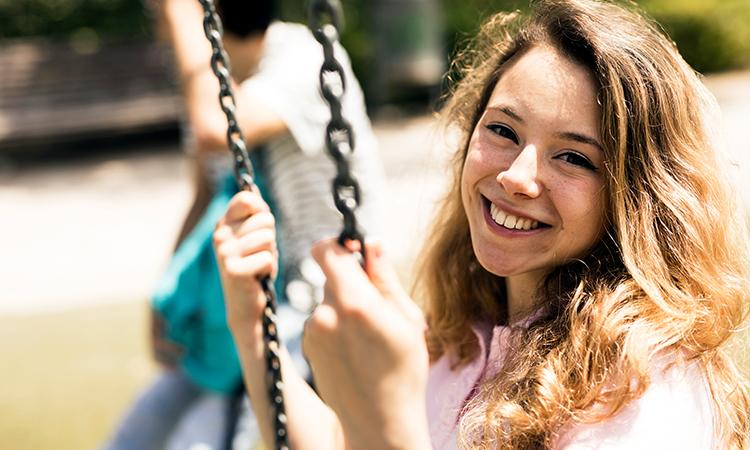Caucasian teenage girl smiling on swings