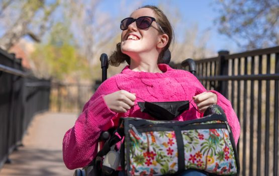 young woman with disabilities in wheelchair with hot pink sweater on and carrying a bag